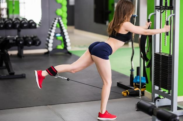 Sexy fitness instructeur met sterk fit lichaam maakt oefeningen in de sportschool met sportsimulator