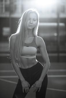 Sexy fitness vrouw met perfect lichaam dragen sport kleding poseren op een tennisbaan in stralen van de zon. zwart-witte kleur