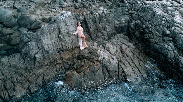 Sexy foto van een mooie brunette poseren terwijl je tussen de rotsen