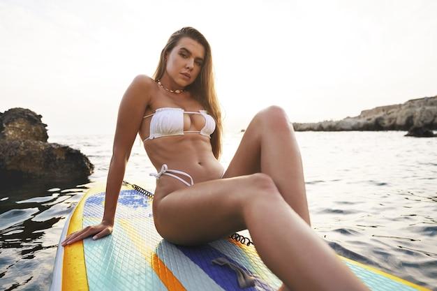 Sexy gelooid meisje in witte bikini staande op sup board