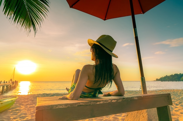 Sexy, geniet en ontspan vrouw draag bikini liggend en zonnebaden op zonnebank op zandstrand op paradijs tropisch eiland onder parasol bij zonsondergang.