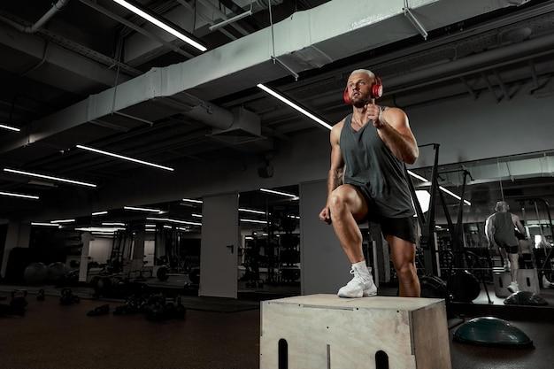 Sexy gespierde mannen met behulp van het platform voor zijn benen op een donkere kleurrijke achtergrond van sportschool.