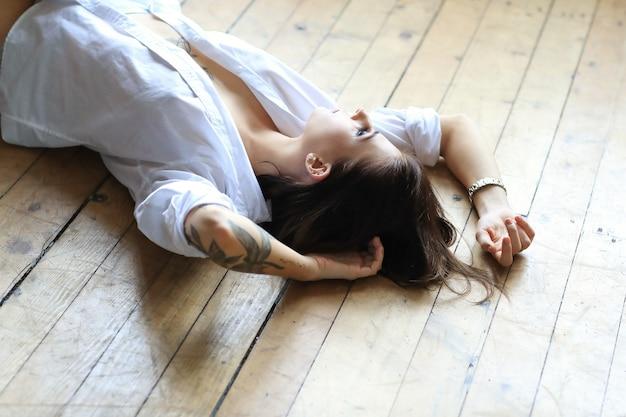 Sexy getatoeëerde vrouw in een wit overhemd liggend op de houten vloer