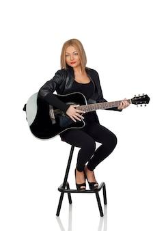 Sexy gitaristzitting met een zwart leerjasje dat op witte achtergrond wordt geïsoleerd