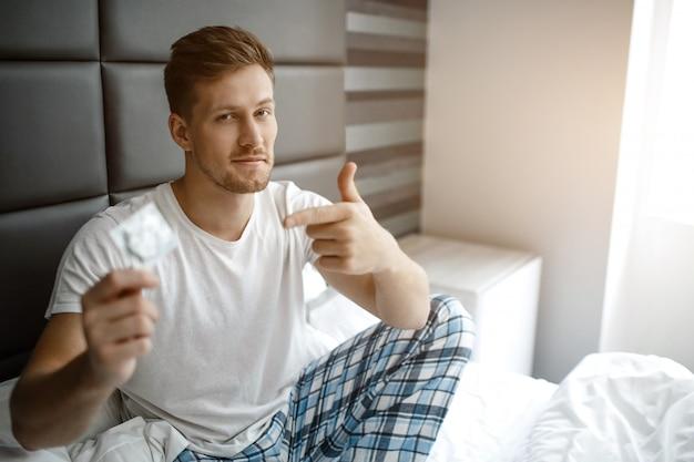 Sexy hete jonge man op bed vroege ochtend. hij kijkt op camera en richt op condoom. guy draagt pyjama.
