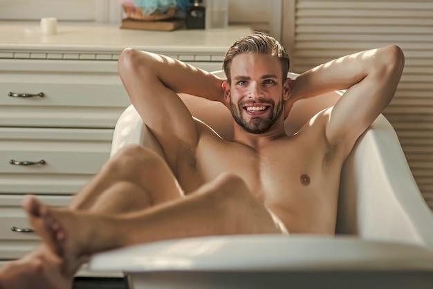 Sexy hipster man ontspannen in de badkamer in een ruime loft interieur studio-appartement. man liggend in badkuip.