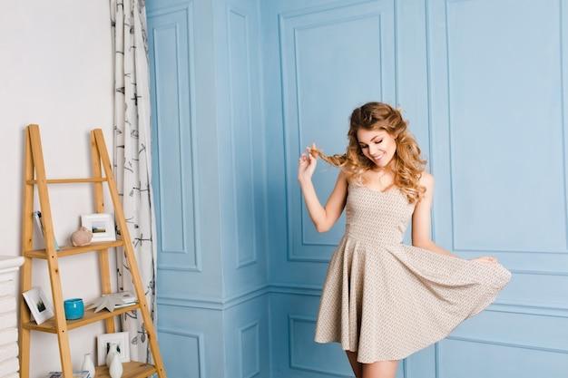 Sexy jong blond meisje met krullend haar haar ogen sluiten en spelen met haar jurk en haar.