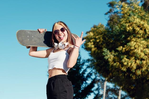 Sexy jong meisje in casual hipster kleding met skateboard achter blauwe hemel met haar tong en stenen borden