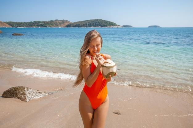 Sexy jong meisje op het strand met verse kokosnoot. zee vakantie.