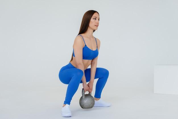 Sexy jong meisje voert sportoefeningen op een witte achtergrond. fitness, gezonde levensstijl.