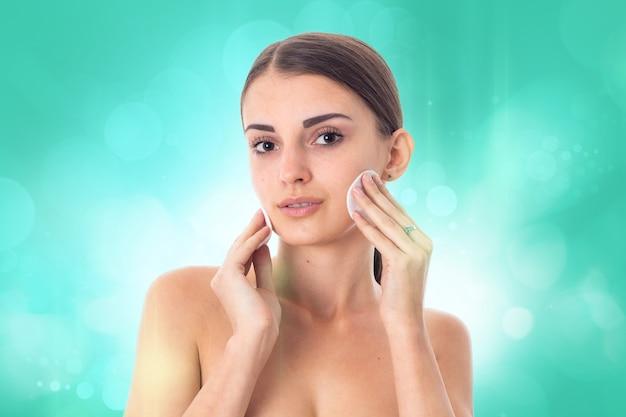 Sexy jong meisje zorgt voor haar huid met reiniging wattenschijfje geïsoleerd op een witte achtergrond. gezondheidszorgconcept. lichaamsverzorgingsconcept. jonge vrouw met een gezonde huid.