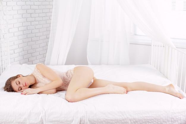 Sexy jong vrouwenmodel die op bed liggen
