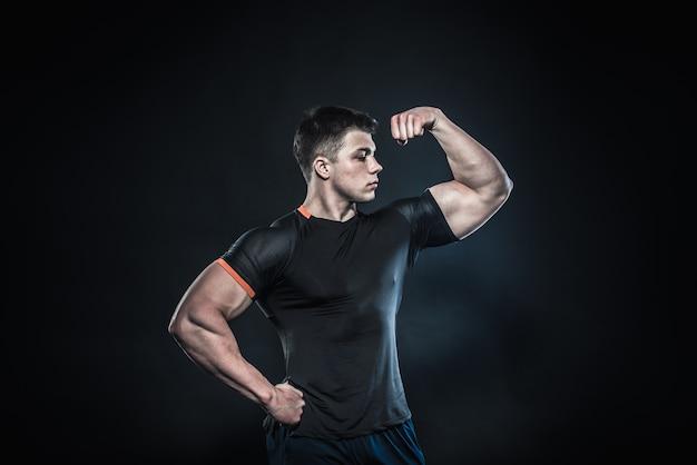 Sexy jonge atleet poseren op een zwarte muur. fitness, bodybuilding