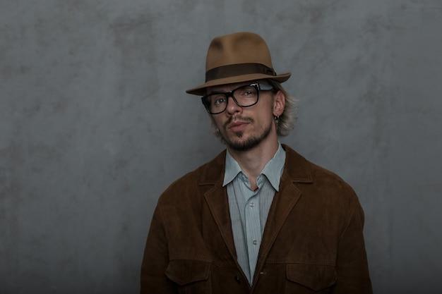 Sexy jonge bebaarde hipster man in trendy bril in een elegante hoed in een modieuze bruine jas in een klassiek gestreept shirt