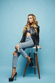 Sexy jonge blonde halfnaakte vrouw in lederen jas en jeans