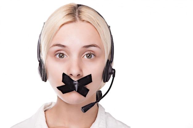 Sexy jonge blonde vrouw in een headset kijkt op en kan niet praten,