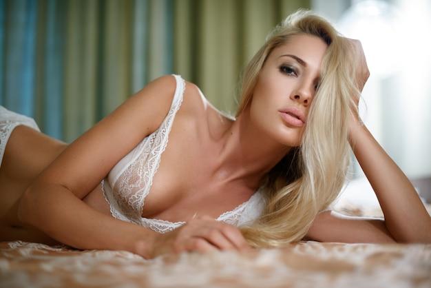 Sexy jonge blonde vrouw liggend op het bed in de slaapkamer in zijn ondergoed