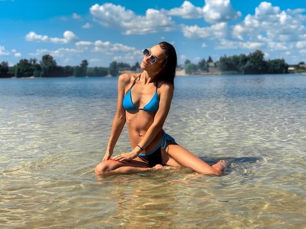 Sexy jonge brunette dame in blauwe zwembroek poseren op het strand in warme zomerdag