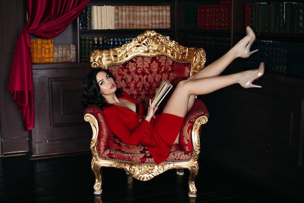 Sexy jonge brunette die op grote leunstoel in bibliotheek ligt.