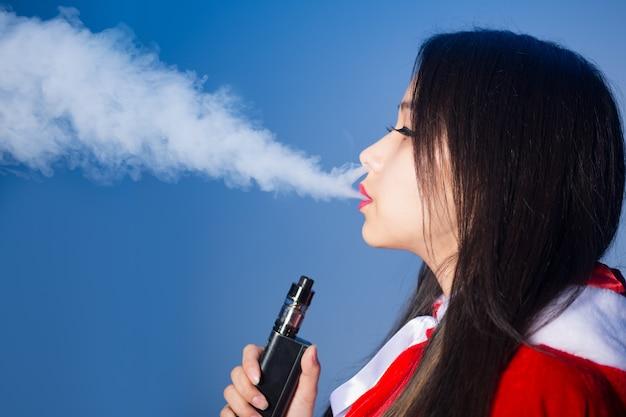 Sexy jonge chinese vrouw in santakostuum die elektronische sigaret houdt en stoom uitademt op blauwe ba...