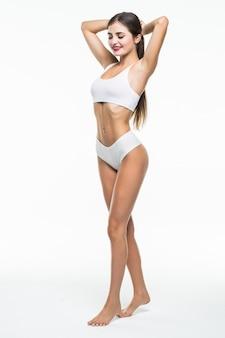 Sexy jonge geïsoleerde vrouw in wit ondergoed op witte muur