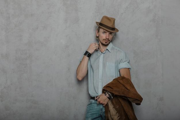Sexy jonge hipster man met lederen armbanden met een jasje in een modieuze hoed in een elegant shirt in spijkerbroek poseren in de studio in de buurt van een betonnen muur. n