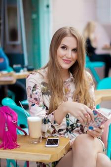 Sexy jonge hipster stijlvolle vrouw zitten in café