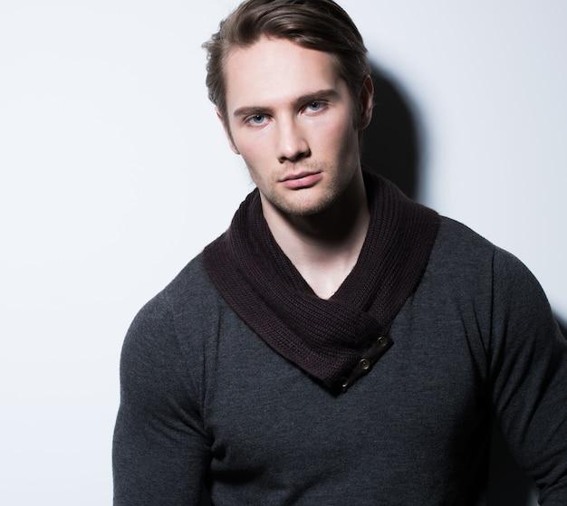 Sexy jonge man in casual poses over muur met contrast schaduwen