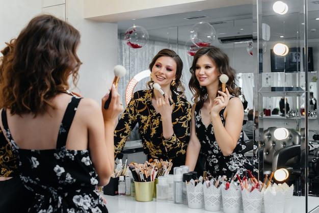 Sexy jonge meiden hebben plezier en maken zich klaar voor een feestje voor de spiegel. mode en schoonheid.