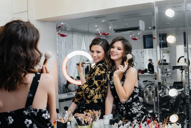 Sexy jonge meisjes hebben plezier en maken zichzelf goed voor een feestje voor de spiegel. mode en schoonheid.