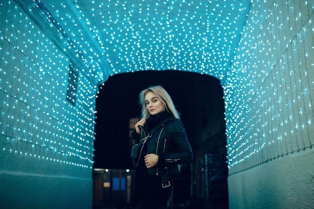 Sexy jonge schoonheid vrouw poseren over nacht stad verlichte straat achtergrond. vakantie vakanties. jonge stijlvolle vrouw blond met lang haar