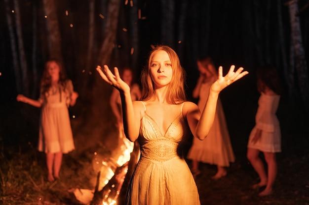 Sexy jonge vrouw die rond het kampvuur danst.