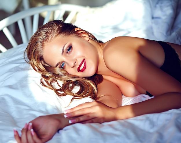 Sexy jonge vrouw die zwarte lingerie draagt die op wit bed in de ochtend ligt