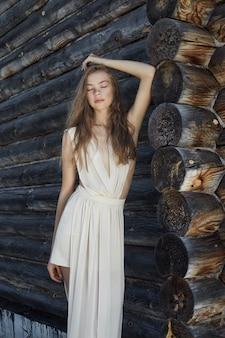 Sexy jonge vrouw in een lichte witte jurk in dorp
