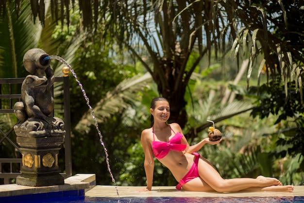 Sexy jonge vrouw in het roze zwempak ontspannen bij pool