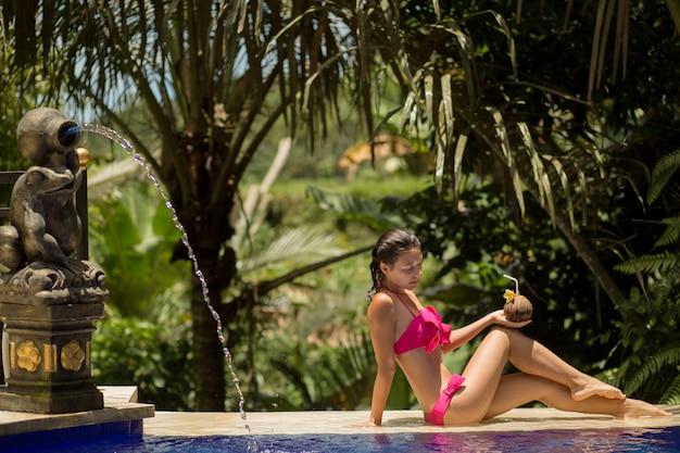 Sexy jonge vrouw in het roze zwempak ontspannen bij pool.