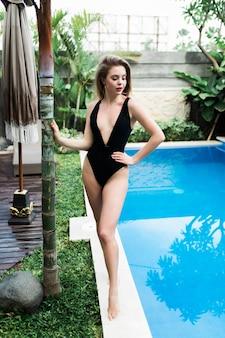 Sexy jonge vrouw in het zwembad met blauw water