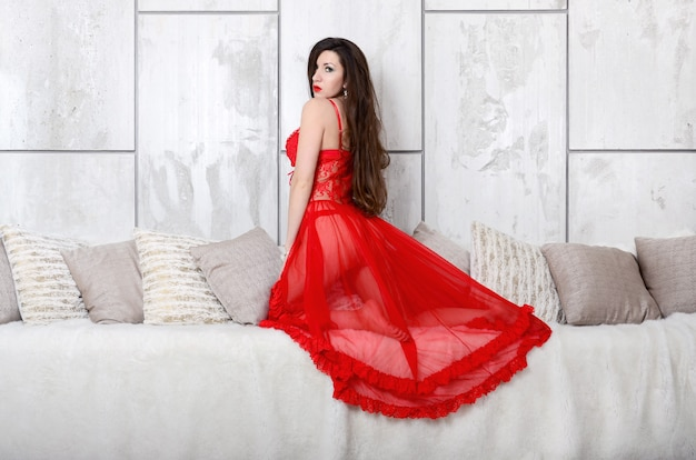 Sexy jonge vrouw in rode peignoir transparante jurk en lingerie naast romige bed met veel kussens