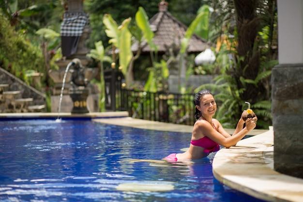 Sexy jonge vrouw in roze zwempak die kokosnotendrank in zwembad op vakantie hebben.