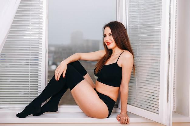 Sexy jonge vrouw in zwarte sensuele lingerie en in kousen poseren
