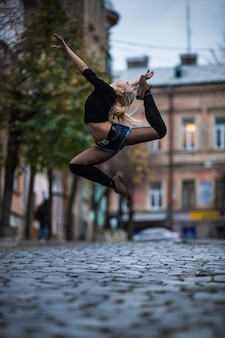 Sexy jonge vrouw in zwembad dansstijl dans buiten in de straat