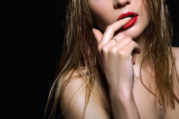 Sexy jonge vrouw met kort nat haar en rode lippen.