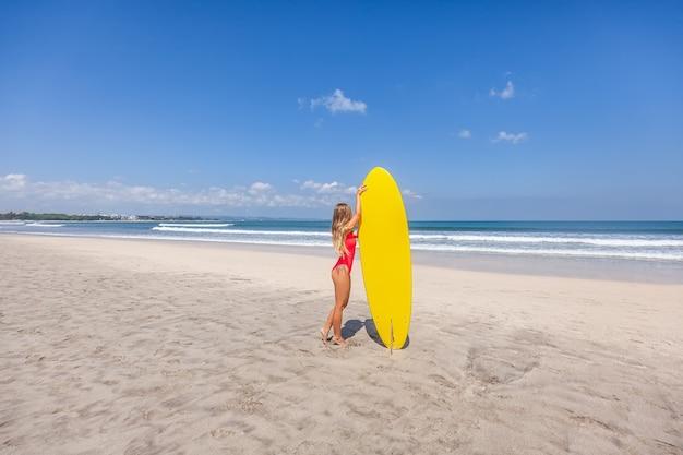 Sexy jonge vrouw met lang haar in rood zwempak met surfplank alleen op strand