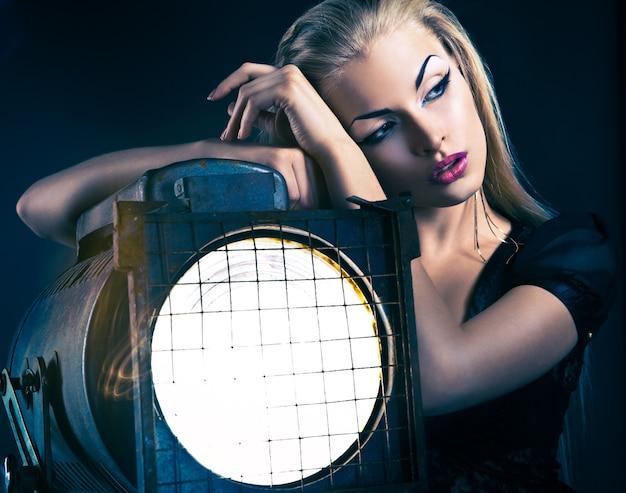 Sexy jonge vrouw met oude schijnwerper over donkere achtergrond