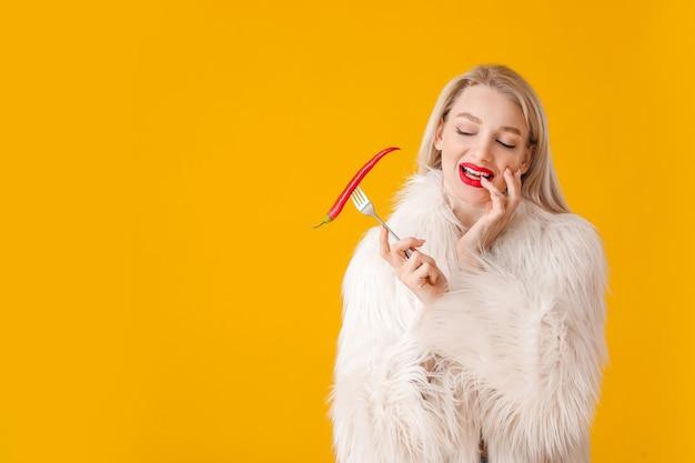 Sexy jonge vrouw met spaanse peperpeper op kleurenoppervlak