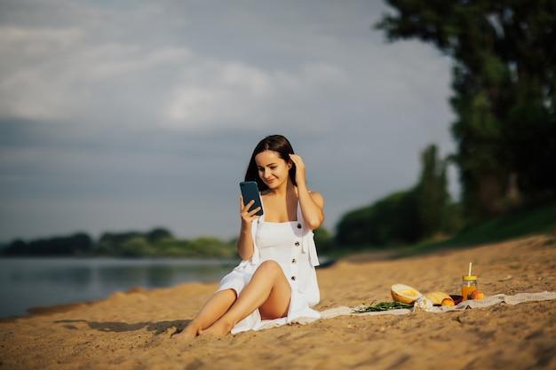 Sexy jonge vrouw op strand met smartphone. ze gebruikt een mobiele telefoon tijdens het picknickfeest op het strand, drinkt sap en eet fruit.