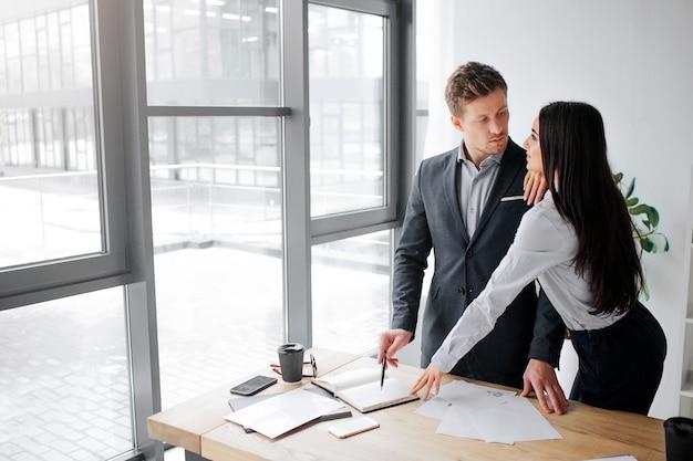 Sexy jonge vrouw staan dicht bij haar baas en kijk naar hem. ze raakt zijn schouder aan.