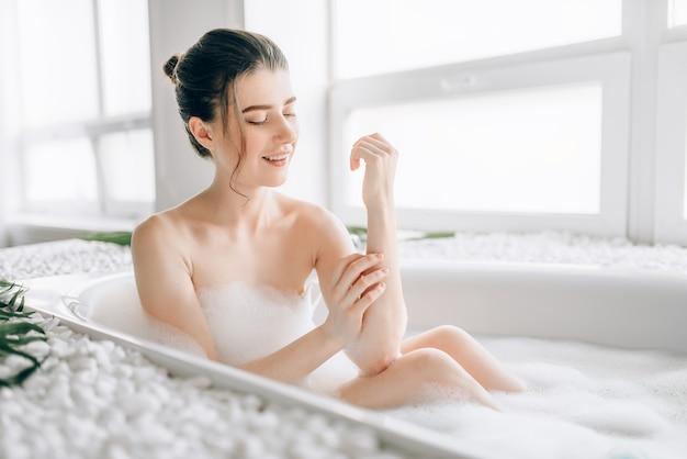 Sexy jonge vrouw wrijft het lichaam met schuim in het bad. luxe badkamer met decor van palmtakken, comfortabel uitrusten