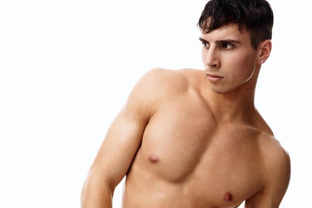 Sexy kerel atleet met een opgepompte torso naakt model lichte achtergrond