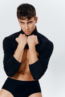 Sexy kerel met een opgepompte torso en kubussen op de buik bodybuilder slipje